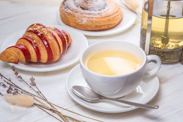 green tea with croissants on white wooden background