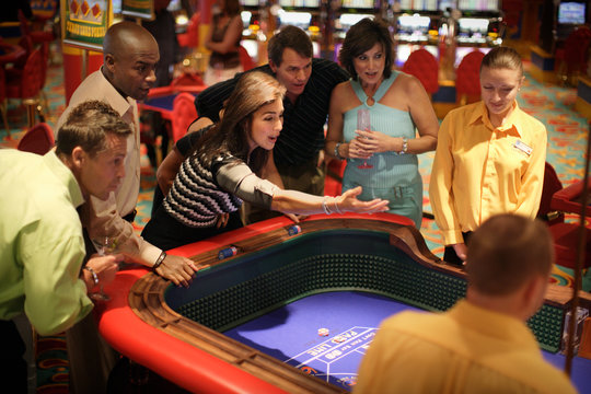 Group of adults at a casino watching in anticipation as a bet is being made by another patron.