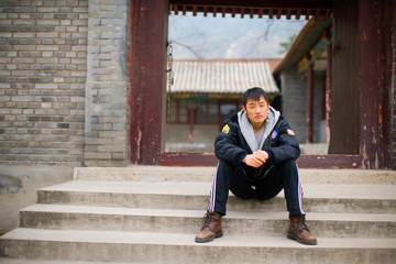 Young man sitting on some steps in front of a traditional Chinese building.