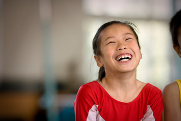 Girl laughing in a gym.