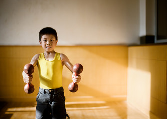 Portrait of a boy lifting weights.