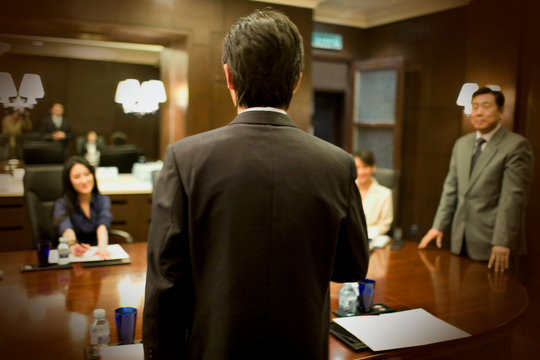 Young adult businessman presenting to colleagues in a boardroom.
