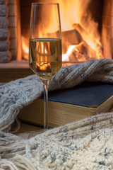 Cozy scene before fireplace with a glass of wine, a book, wool scarf.