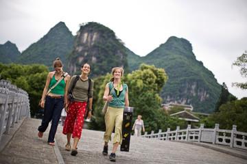 Portrait of three smiling female tourists walking along an urban street.