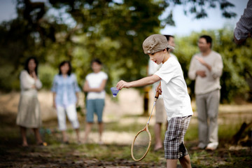Young boy playing badminton outdoors.