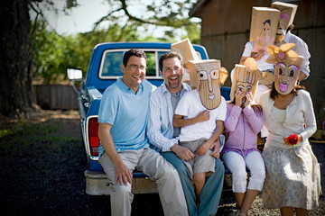 Portrait of two smiling mid-adult men sitting with their family who are wearing paper bag masks on the back of a truck.