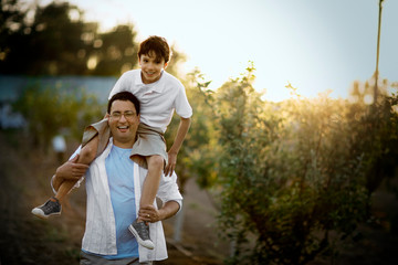 Portrait of a smiling mid-adult man holding his son on his shoulders while standing in an apple orchard.