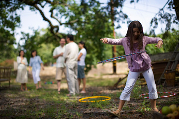 A young girl hula-hooping while her family stand in the background