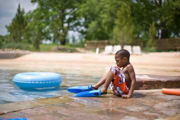 Young boy sitting at the edge of a swimming pool wearing flippers.