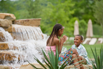 Young boy and his teenage sister having fun while sitting next to a small waterfall.