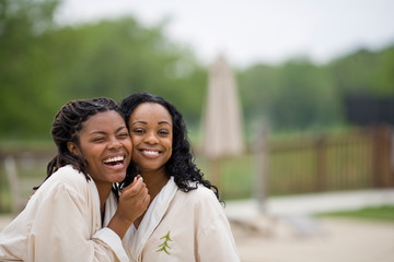 Portrait of two laughing young women wearing bathrobes.