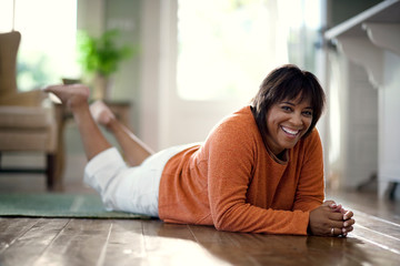 Portrait of a woman lying down relaxing on hardwood living room floor.