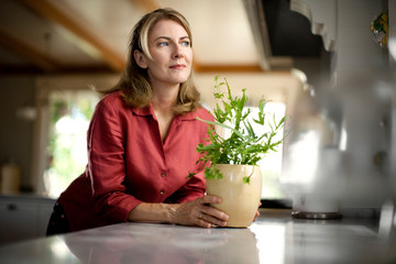 Woman holding a pot plant on a kitchen counter and looking out of the window.