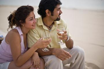 Couple enjoying a glass of wine on the beach
