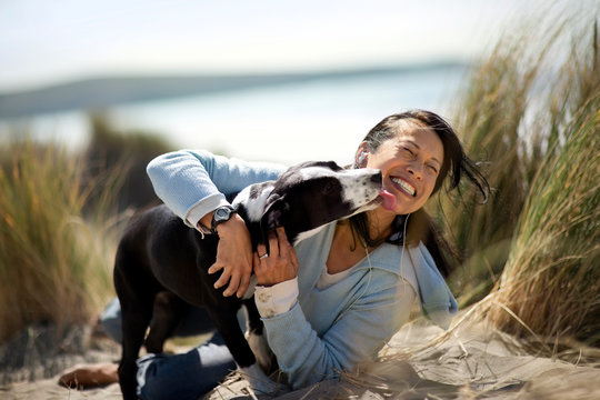 Happy middle aged woman playing with her dog at the beach.