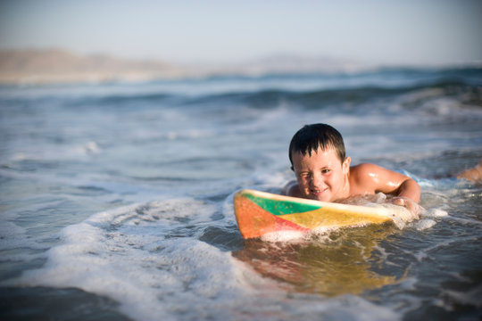 Young boy lying on a surfboard in the ocean.