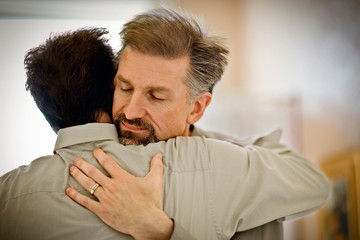 Mid-adult man hugging his partner.