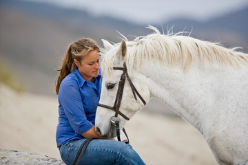 Young woman with a white horse on the beach.