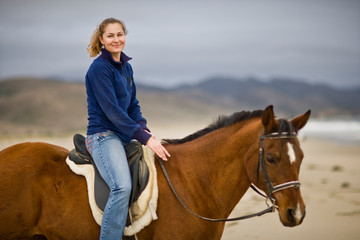 Portrait of a young woman riding a brown horse on the beach.