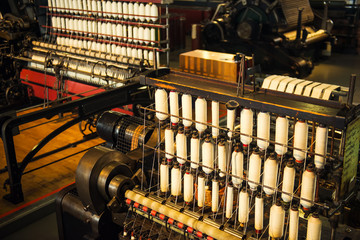 Rows of white cotton threads on vintage automatic loom. The concept of historical development of weaving in England. Selective focus. Copy space.