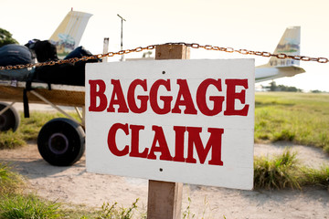 Baggage claim sign on the fence of a rural airstrip.