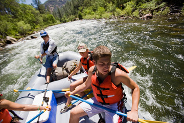 Teenage boy and friends rafting along a river.