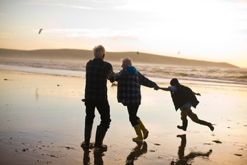 Grandparents having fun while holding hands with their grandson on a beach at sunset.
