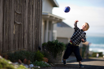 Young boy playing outside with a toy football.
