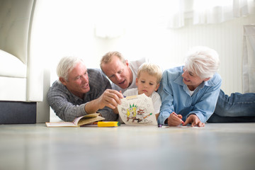 Young boy sitting on the floor with his grandparents and father while coloring in.