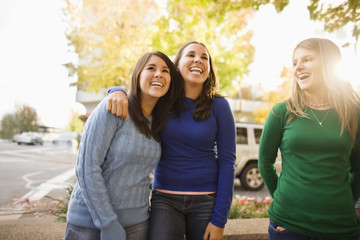 Three laughing young woman standing side by side on a suburban street.