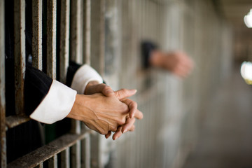 Hands of a mid-adult woman through bars of a prison cell in a derelict building.