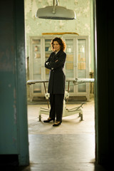 Portrait of a mid-adult business woman standing in front of a table in an old operating room.