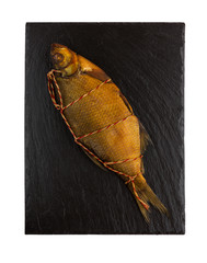Smoked bream on a slate board. Bream on black surface of slate isolated on white background. Top view.
