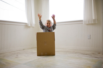 Boy jumping out of box in house