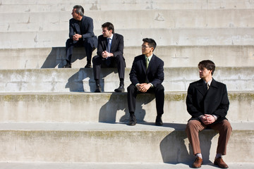 Four businessmen sitting on steps outside a building.