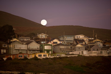 Full moon appearing above row of houses