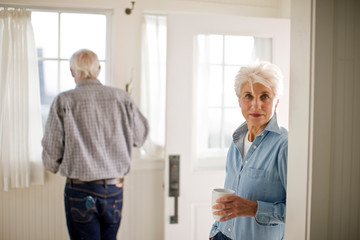 Portrait of a senior woman drinking coffee as her husband looks out a window.