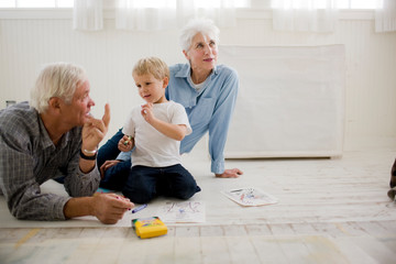 Senior couple sitting on the floor playing with their young grandson.