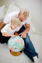 Father pointing out places on a globe to his son
