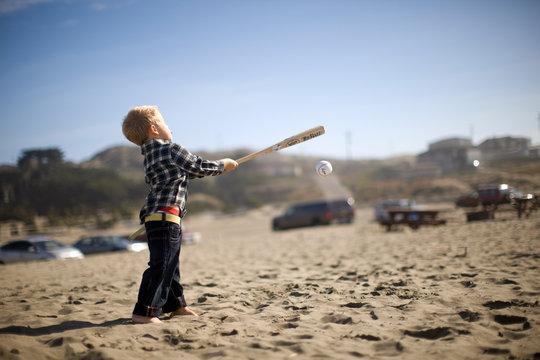 Young boy playing softball on a beach