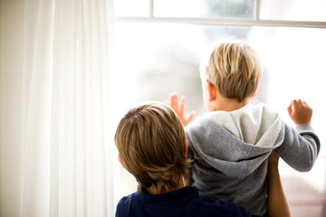 Two brothers looking out the window of their home.
