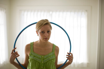 Portrait of a young adult woman with a hula-hoop in a room.