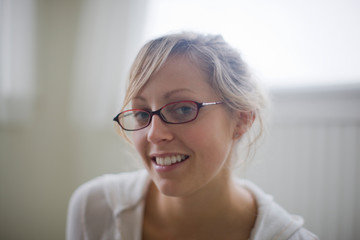 Portrait of young adult woman wearing glasses in a room.