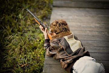 Boy aiming a shotgun while lying on his stomach on top of a wooden footbridge.