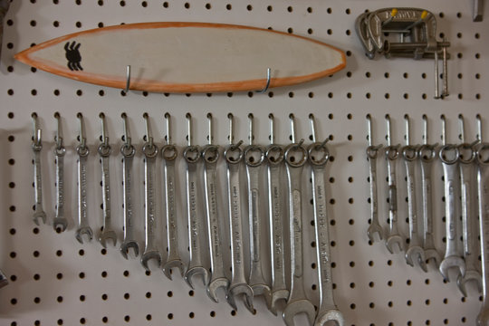 Different sized silver spanners hanging in a row on a perforated board.