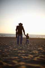 Man walking on beach holding son and guitar