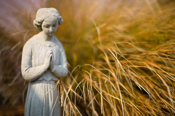 Serene stone statue next to a grass bush.