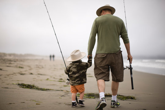 Young boy and his father walking along a beach carrying fishing rods and wearing hats.