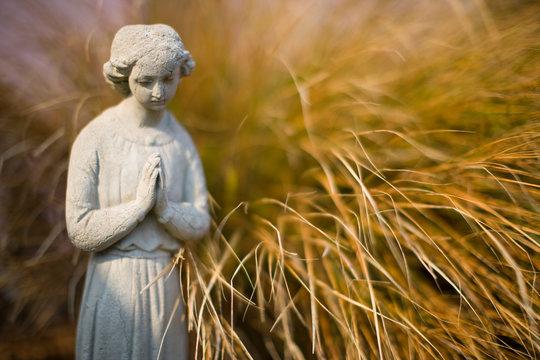 Serene stone statue next to a grass bush.