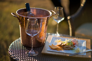 Ice bucket on table with wineglasses and appetisers